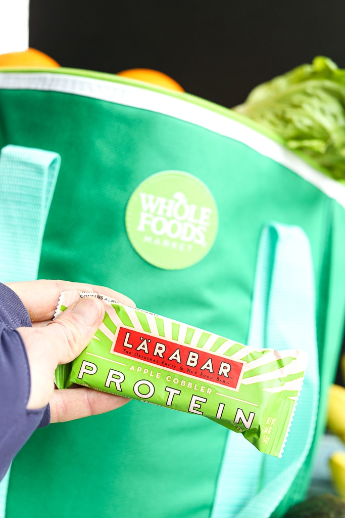 A Larabar protein bar in front of a bag of groceries from Whole Foods