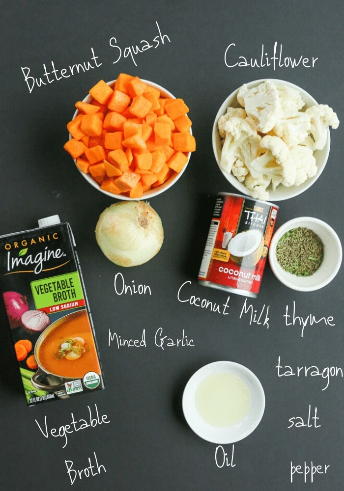 all ingredients on a black board labeled with white writing: chopped butternut squash, chopped cauliflower, onion, can of coconut milk, spices, oil, and a box of vegetable broth