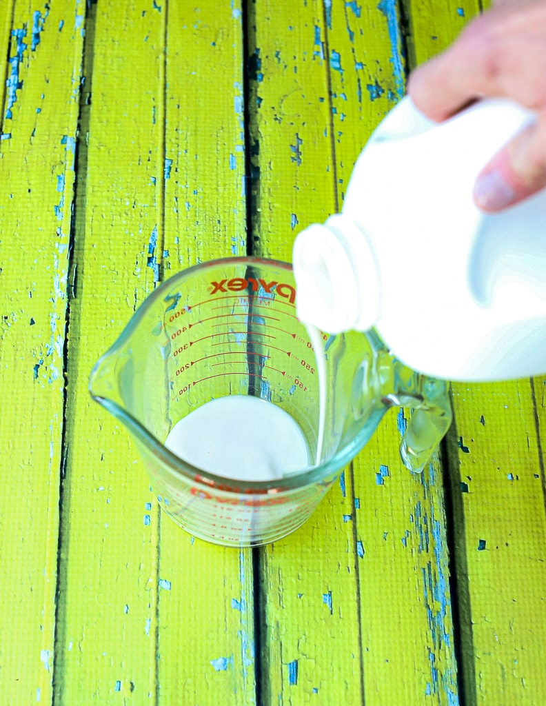 pouring milk into a glass measuring cup