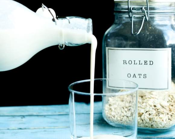 Oat milk being poured into a glass with rolled oats in the background