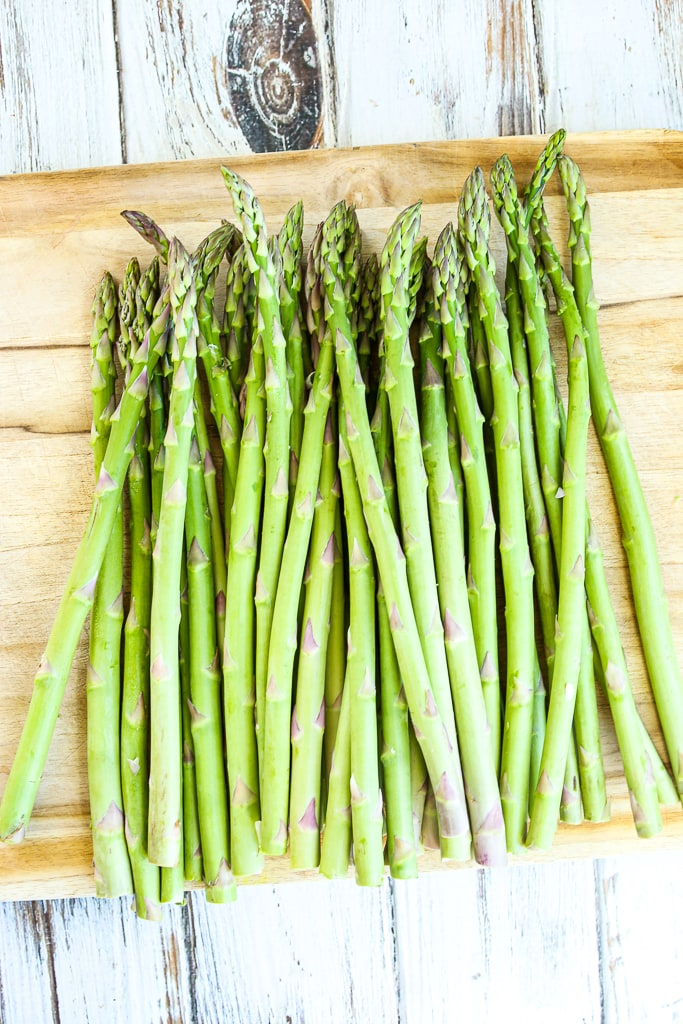raw asparagus on a cutting board