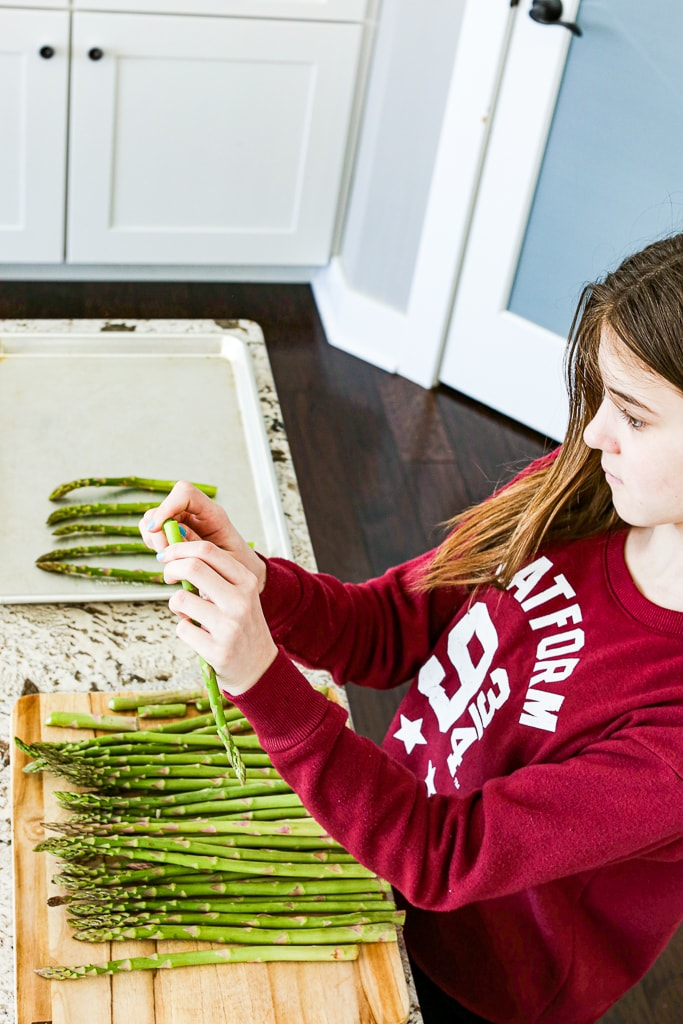 Meghan helping prepare the baked asparagus by bending and snapping off the ends.