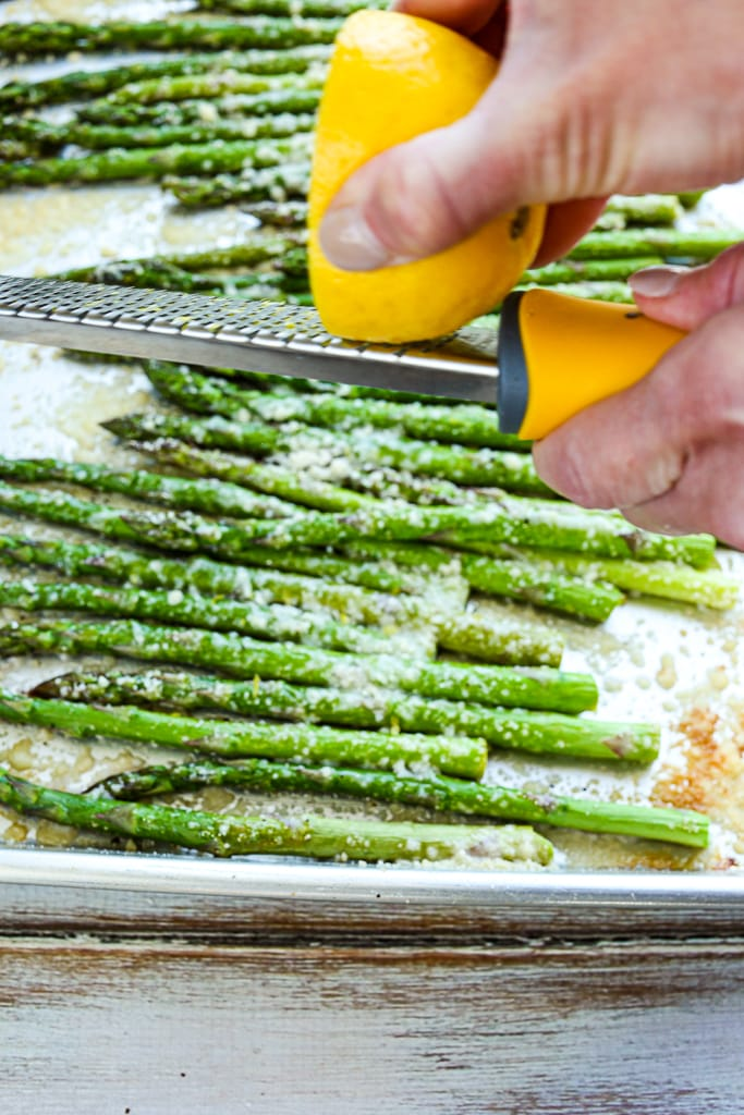 using a zester to add lemon zest to baked asparagus on a baking sheet