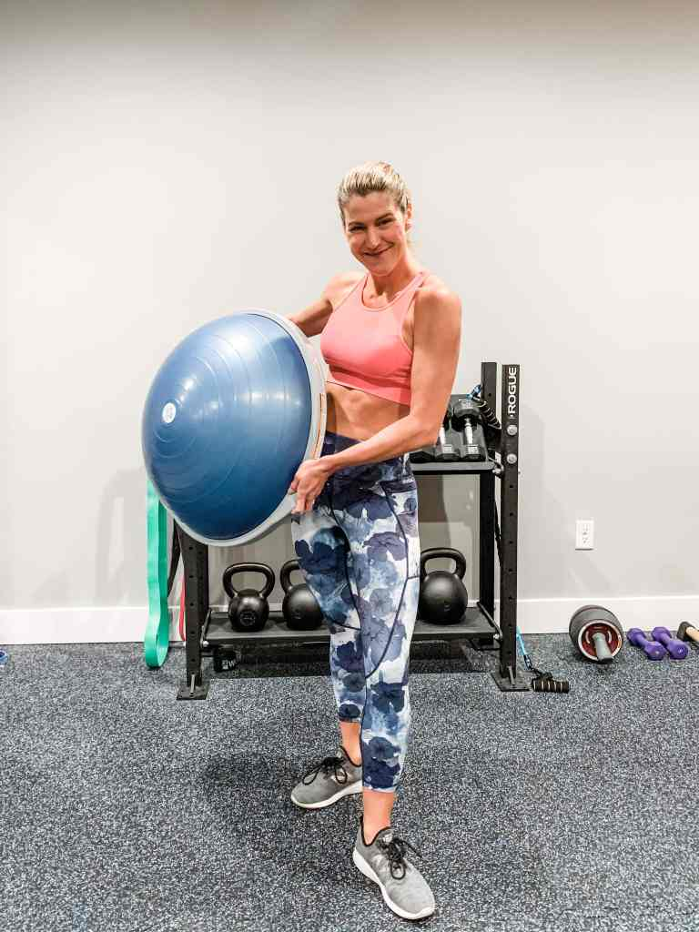 A woman in floral leggings and a sports bra holding a bosu ball in a home gym