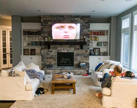 a family in the living room watching a movie on a large screen above fireplace showing Sandlot movie