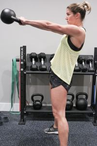 a side view of a woman completing a kettlebell swing