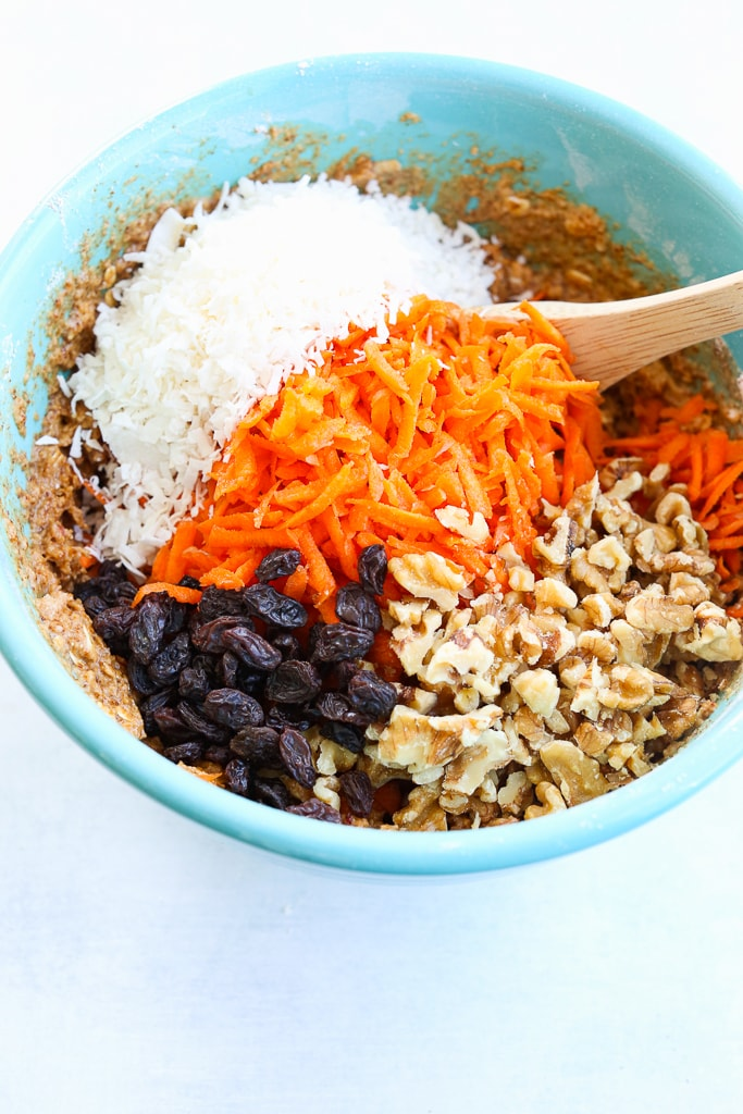 Shredded Carrots, coconut, raisins, and walnuts being folded into batter with a wooden spoon in a turquoise bowl