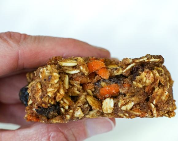 A bite taken out of a cookie with pieces of oats and carrot showing