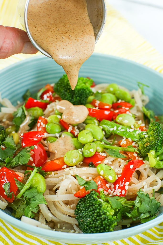 pouring sauce on top of a prepared Vegan Asian Noodle Bowl