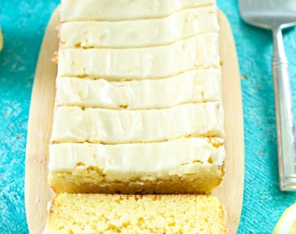overhead shot of a sliced lemon loaf cake with lemon glaze and cut lemons, plates, and a spatula