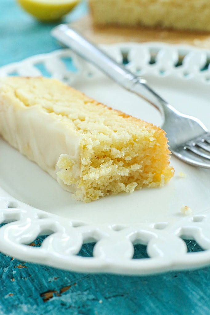 a piece of lemon loaf cake with a bite taken out on a white plate with a fork.