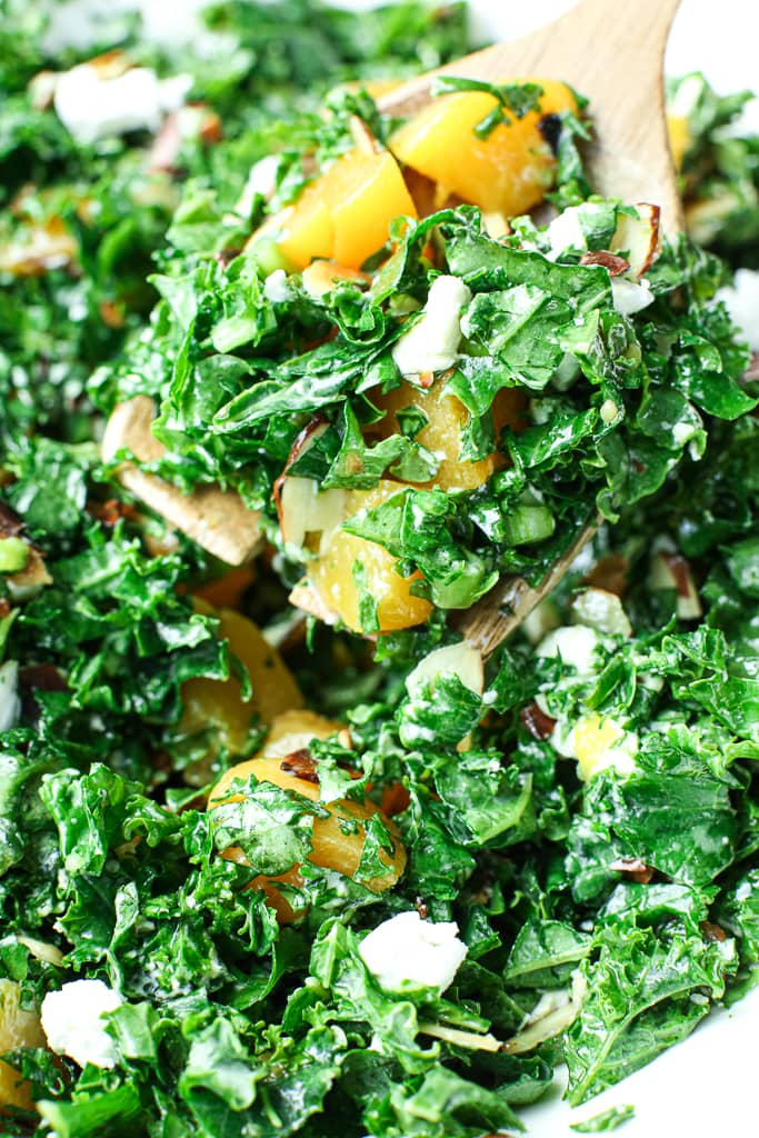 close up picture of easy kale salad being served with a serving spoon