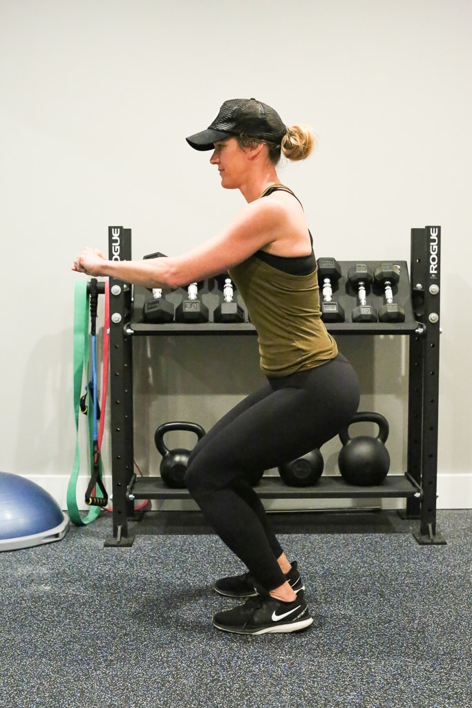 a woman doing squat with no weights