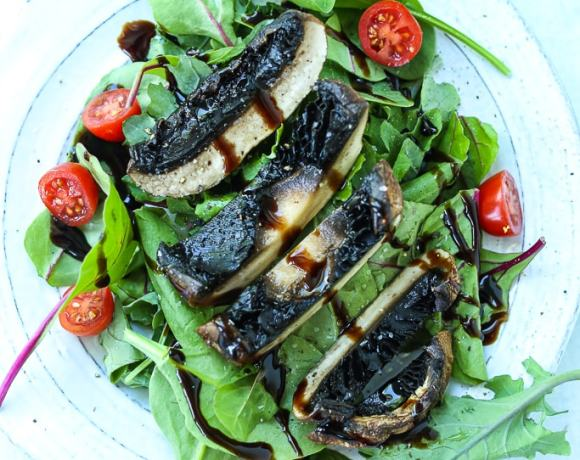 an overhead shot of salad with tomatoes and a cut grilled portobello mushroom