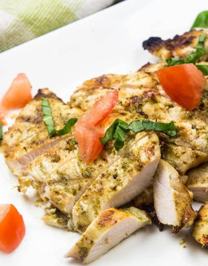 a plate of chicken with basil and tomatoes on top
