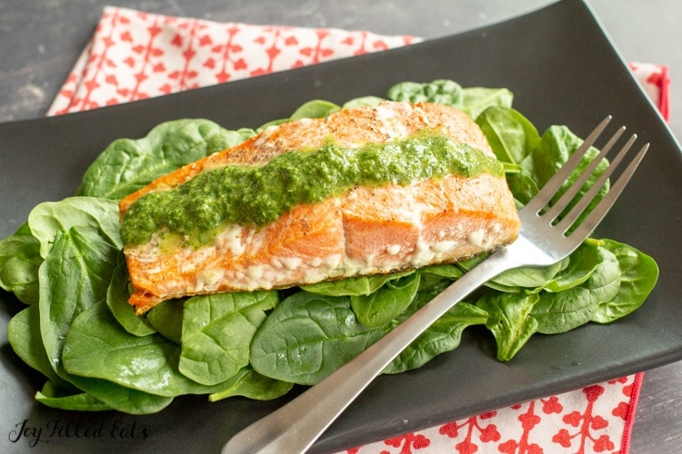 a black plate with salmon and a bed of greens and topped with green pesto sauce