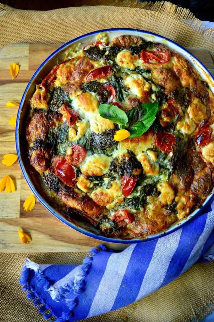An overhead shot of breakfast strata with a. blue striped napkin curled around the pan