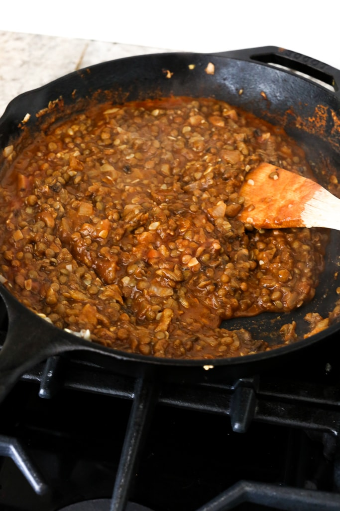 lentil taco mixture cooking in a pan and a wooden spoon