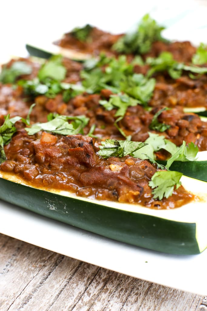 close up picture of a zucchini boat stuffed with a taco lentil mixture and topped with cilantro