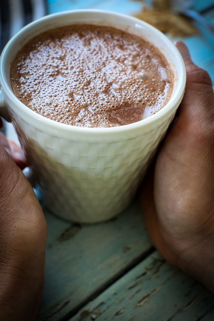A woman's hands holding a cup of hot cocoa