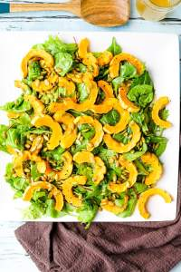 an overhead shot of roasted deletica squash salad on a white plate