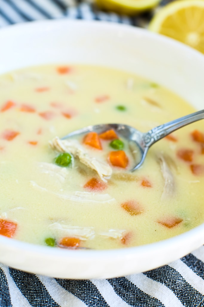 a spoonful of Greek Lemon Chicken soup coming out of bowl
