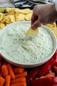 caramelized onion dip with a chip being dipped in and surrounded by chips and veggies