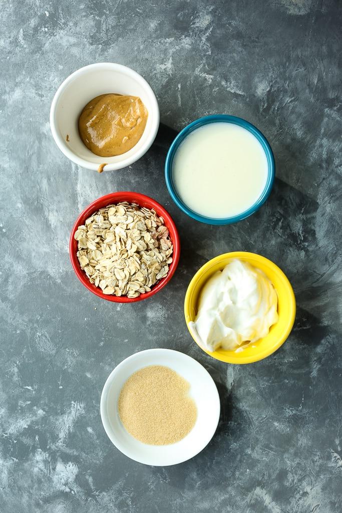 overhead shot of recipe ingredients--oats, Greek yogurt, golden monkfruit sweetener milk, and peanut butter