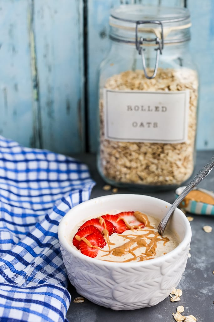 a bowl of peanut butter overnight oats with a jar of old fashioned rolled oats in the background
