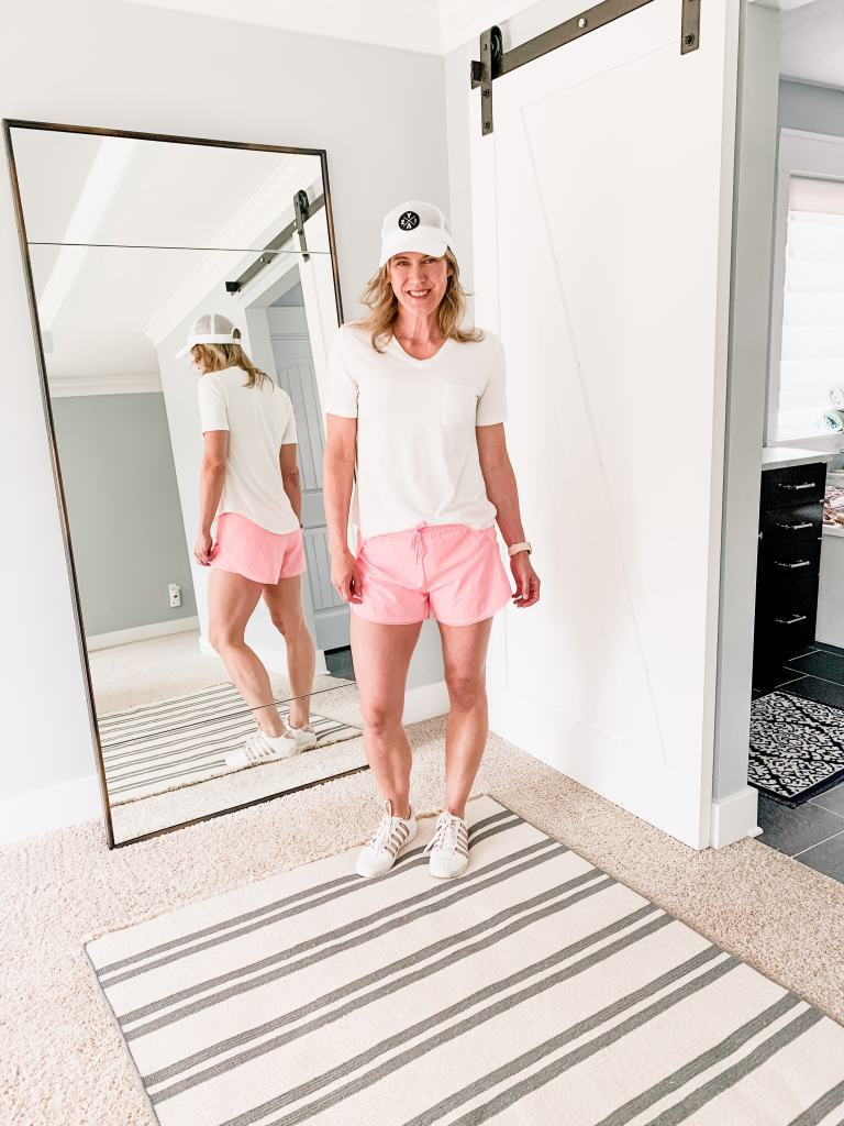 woman in pink shorts and white tee shirt with a hat on