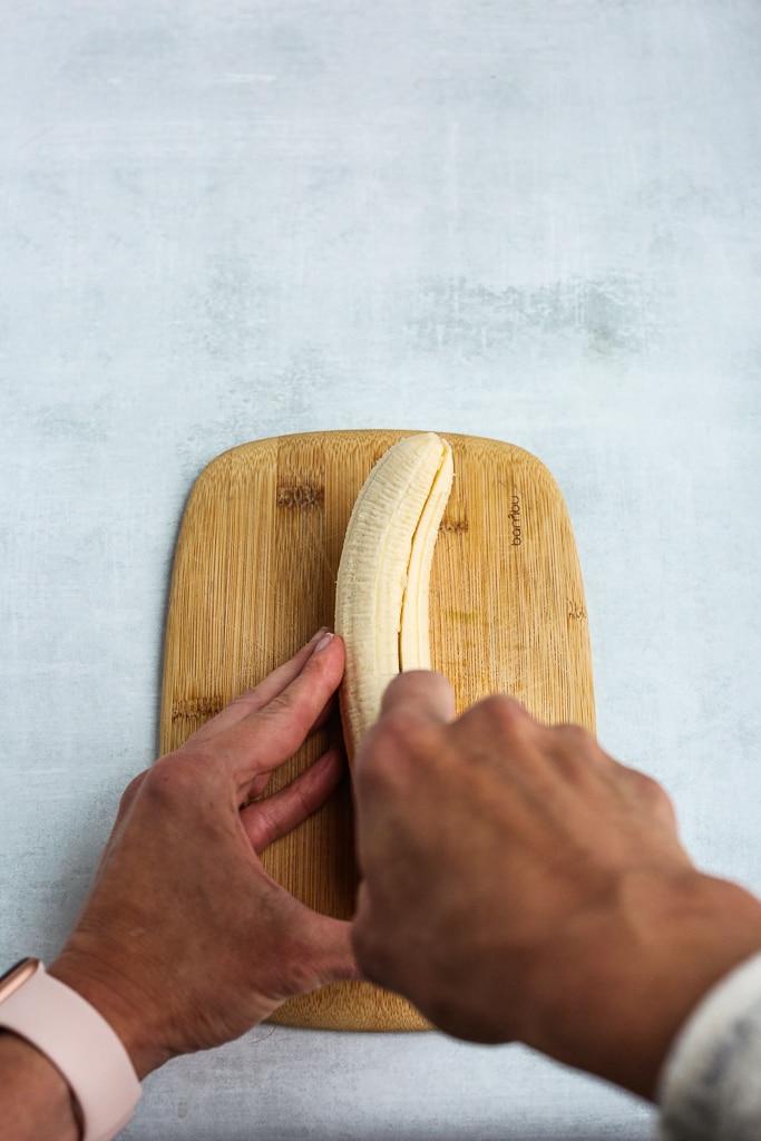 slicing a banana in half on a cutting board