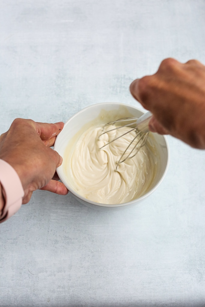 whisking yogurt in a white bowl