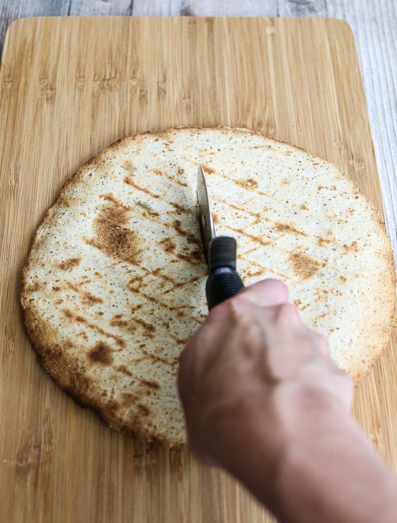 slicing the Grilled Zucchini Quesadilla with a pizza cutter