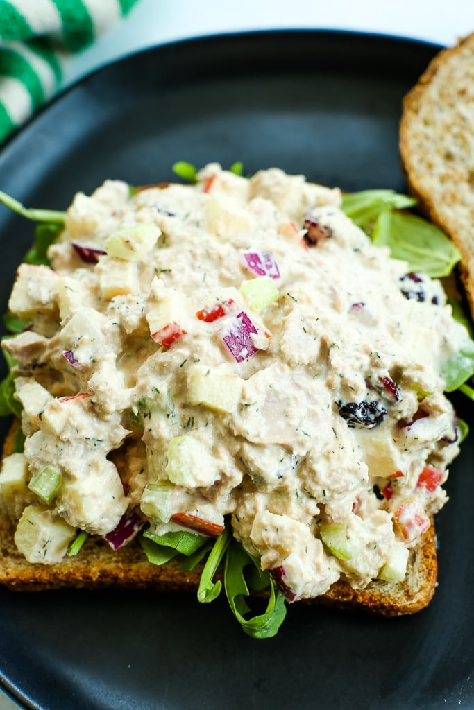 an open faced sandwich with apple cranberry tuna salad