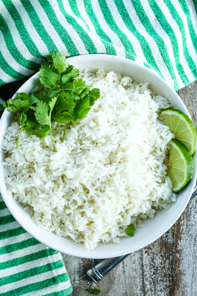 a white bowl of coconut rice recipe with cilantro and lime