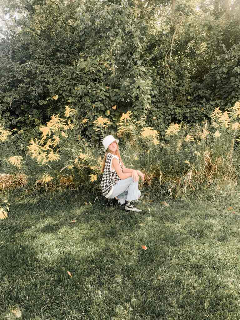 a young girl in jeans squatting in front of yellow flowers