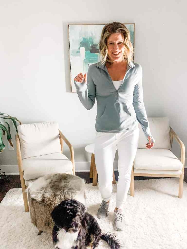 a woman in white joggers with a gray pullover and a dog