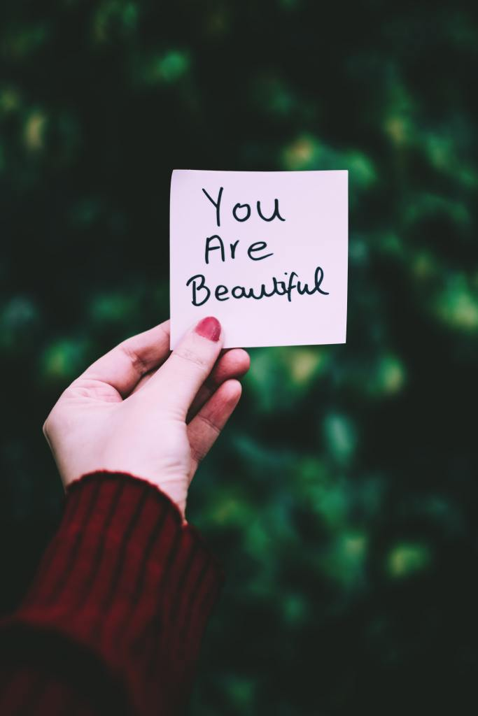 Holding a Note That Says You Are Beautiful to Boost Confidence