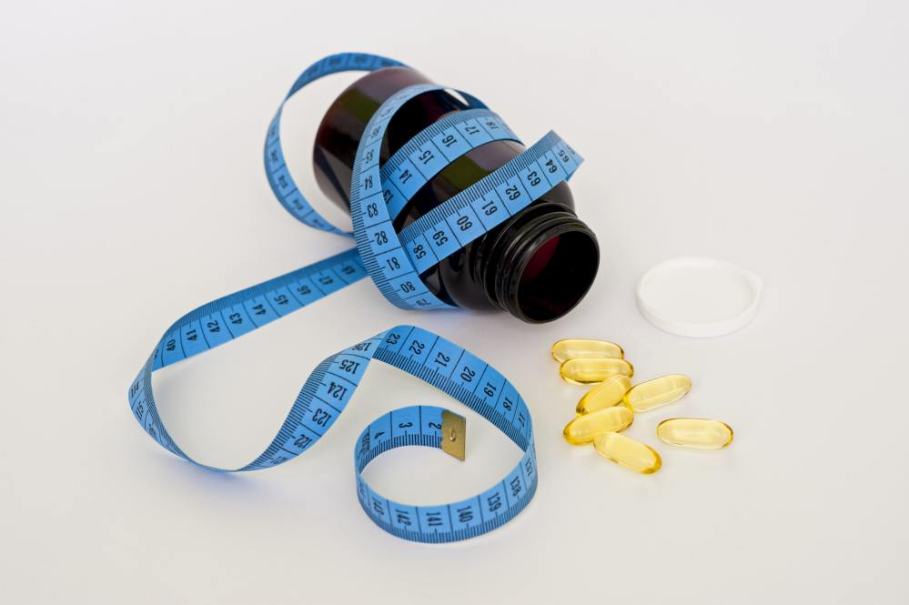 Bottle of Diet Pills with Tape Measure Around It