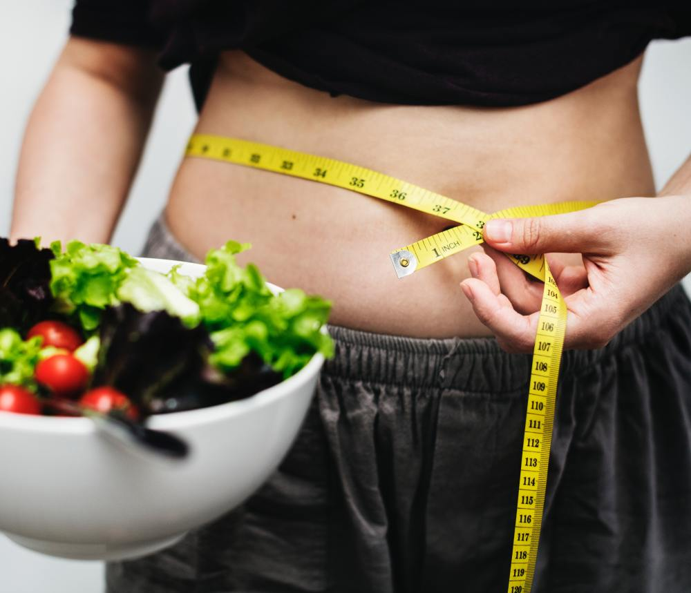 Person with Tape Measure Around Waist Holding a Salad for Meal Skipping