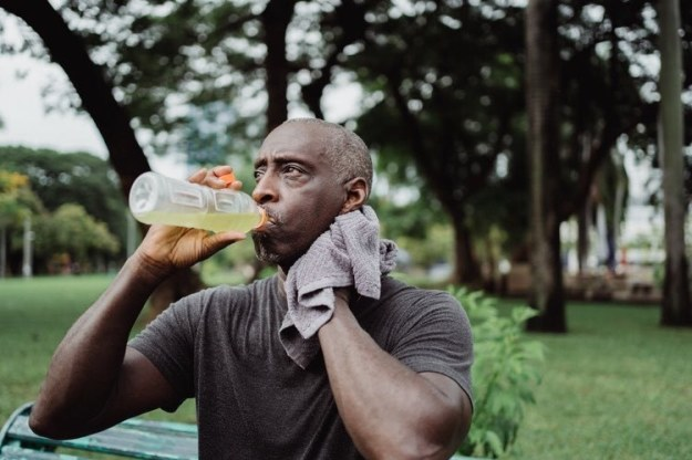 Man With a Towel Drinking A Sports Drink