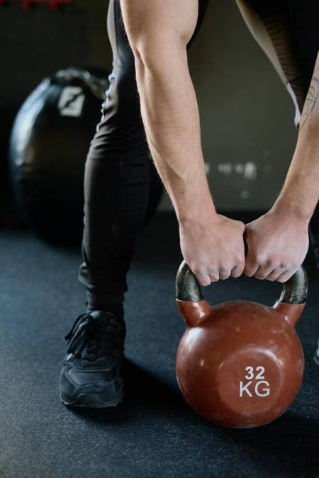 Man With Hands On A Kettlebell