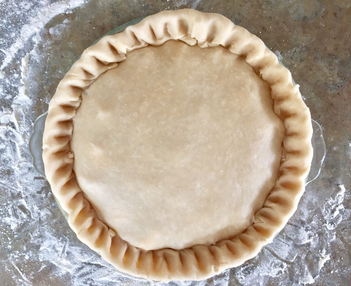 A second pie crust is fitted to cover the cherry filling.