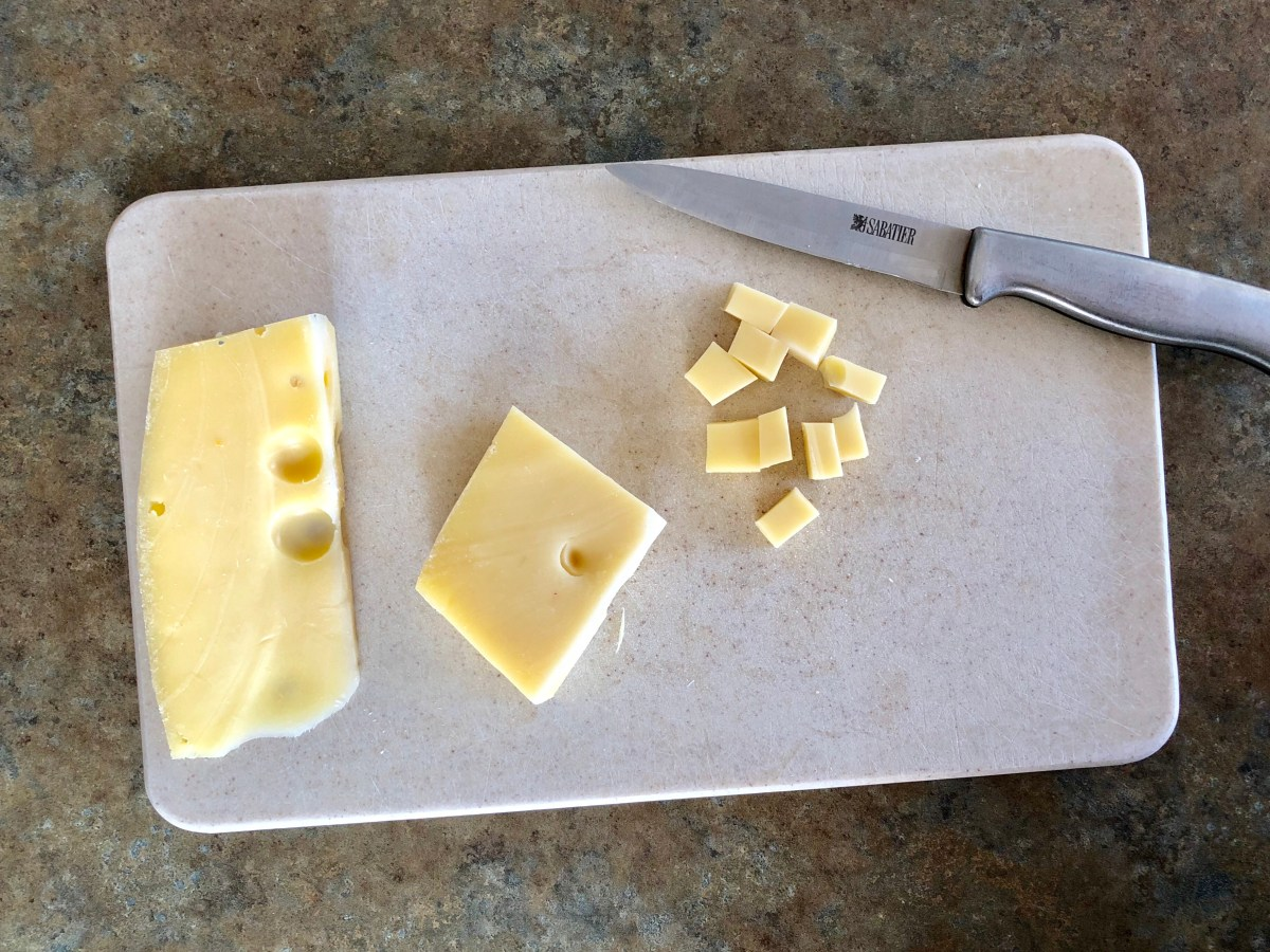 Divide the cheese in half. Cut one half into bitesize cubes and shred the other half with a cheese grater.