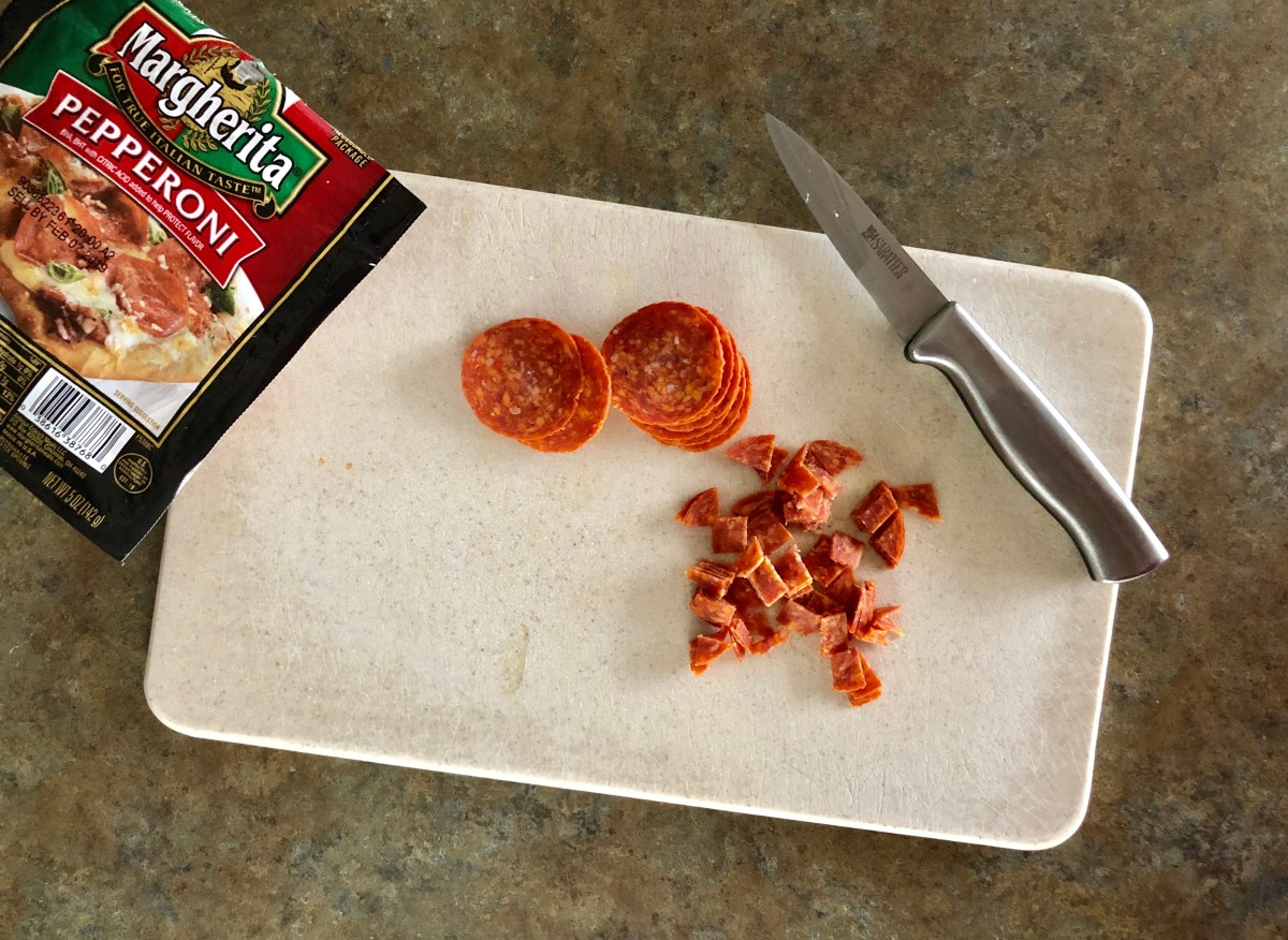 Diced pepperoni on a cutting board.