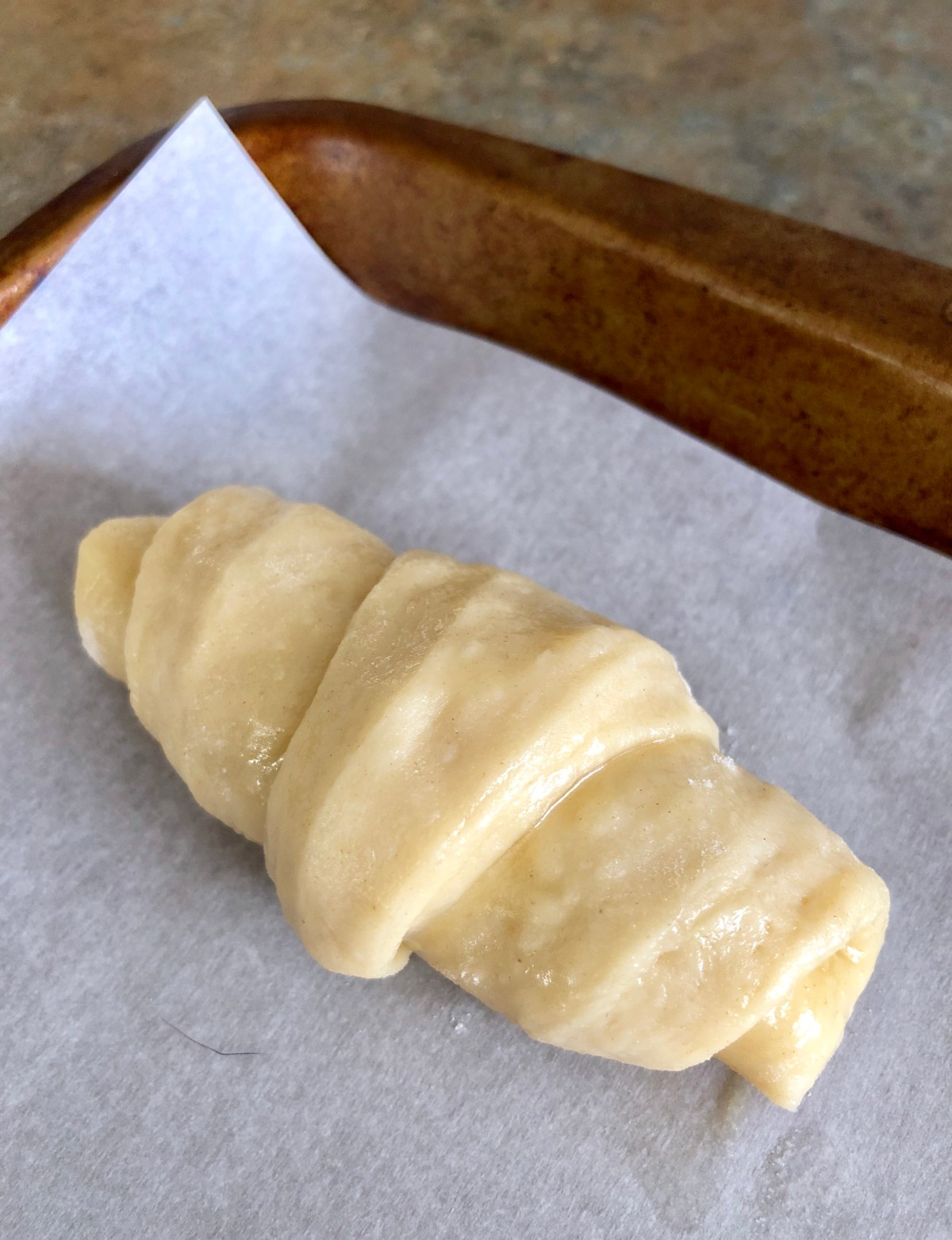 Crescent roll on a parchment lined baking sheet.