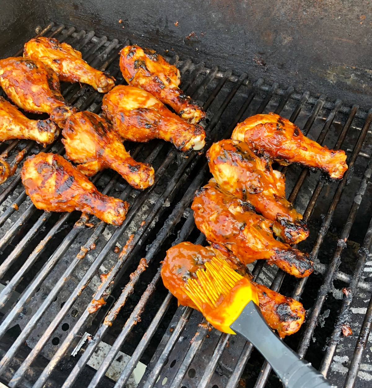 Chicken drumsticks cooking on a grill rack.