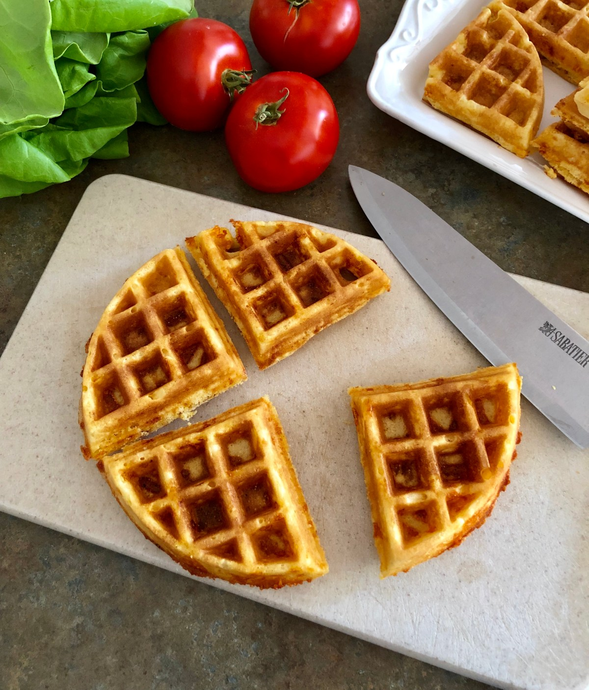 Round waffle cut into fourths on a cutting board.