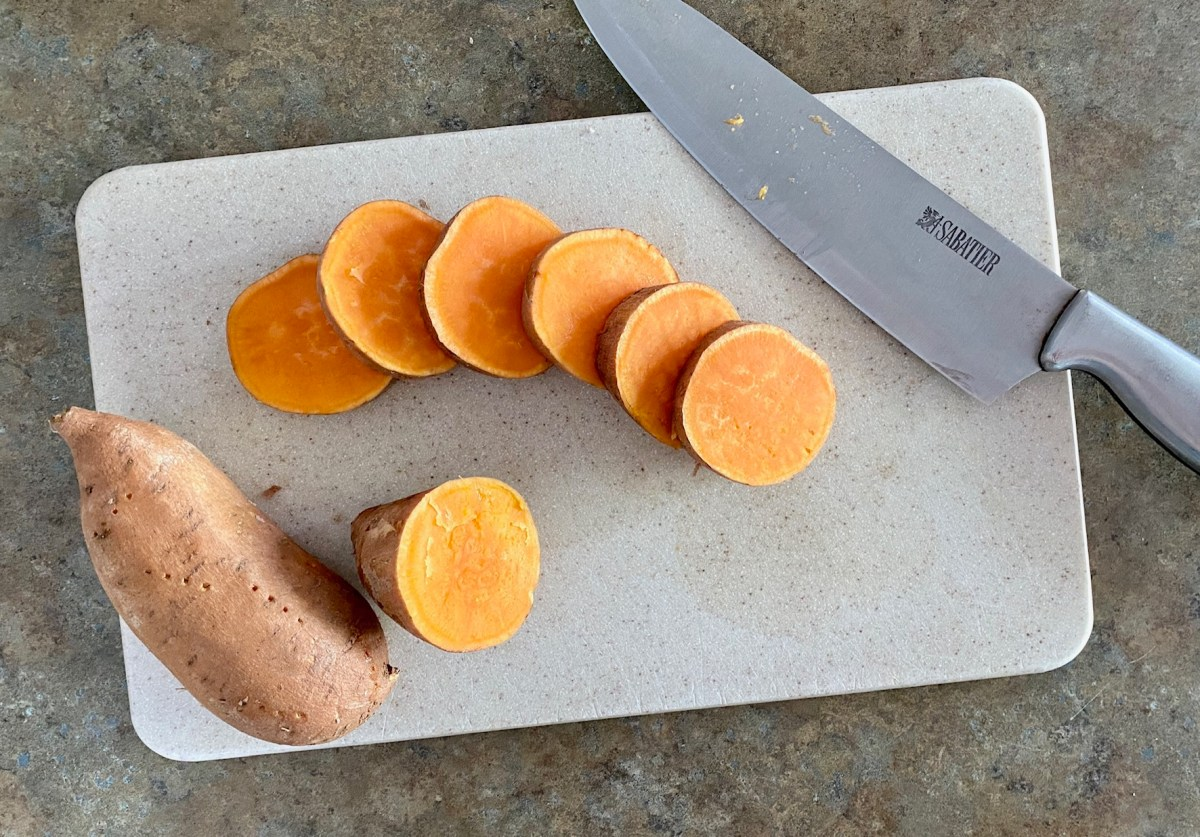 Sweet potatoes sliced into 1/2 inch thick rounds on a cutting board. #sweetpoatoes #grilledsweetpotatoes #grillrecipes #healthyrecipes #healthydinnerrecipes #cookoutrecipes #summerfood