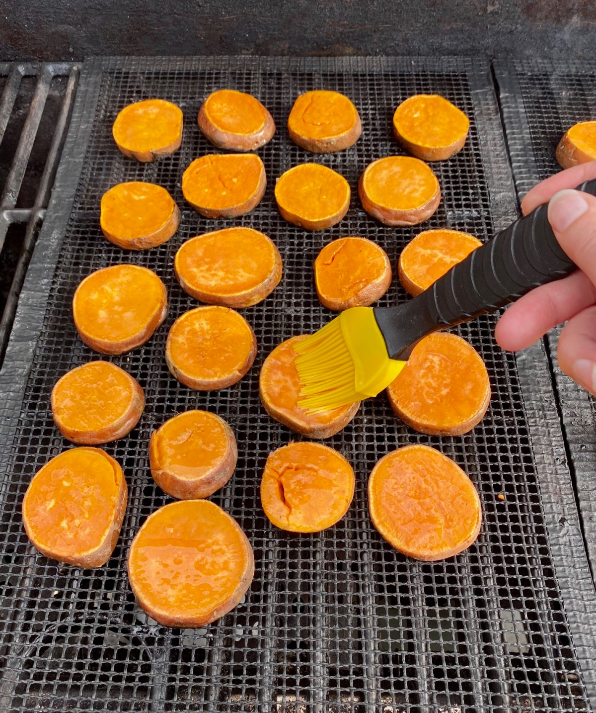 Sweet potato rounds cooking on a grill mat over medium heat. #sweetpotatoes #grilledsweetpotatoes #sweetpotatorecipes #howtogrillsweetpotatoes #howtogrillpotatoes #potatorecipes #potatoesonthegrill